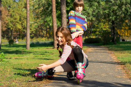A little boy raises his sister who fell on roller skates. The boy helps the girl who fell, rolling on rollers in a park. Stock Photo