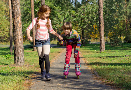 The girl helps the boy to roller-skate. The sister supports a brother who learns rollerblading