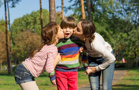 Mom and sister kiss the boy from both sides in the park