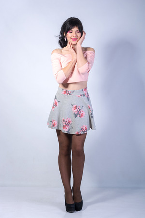 Young woman with a heart on her cheek in a mini skirt smiles on a white background