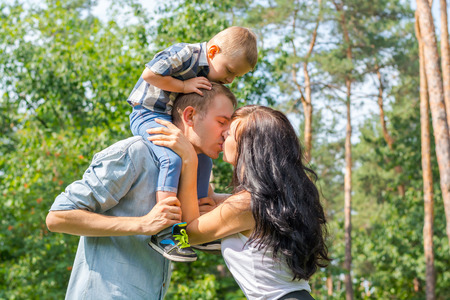 Mom kisses daddy who keeps their child on their shoulders Imagens