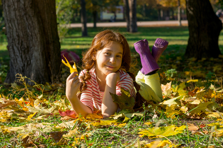 A red-haired girl in rubber boots lies on the yellow leaves in the park in the fall. Girl holding yellow leaf in hand