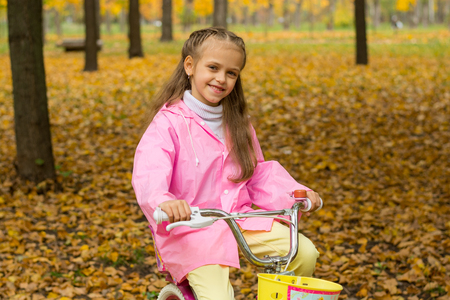 Little girl in a pink raincoat is riding a bike in the autumn park