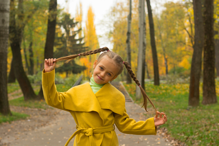 The girl is holding herself for the pigtails. Little girl in a yellow coat standing in autumn park.