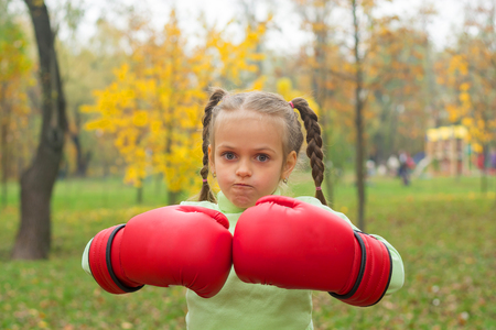 A little girl in huge boxing gloves makes an evil face. A little girl in huge boxing in a park.