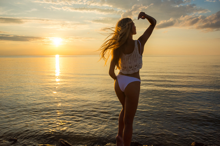 Beautiful happy young woman stands a back in a swimsuit at the sea background at the sunset