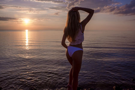 Beautiful happy young woman stands a back in a pink swimsuit at the sea background at the sunset