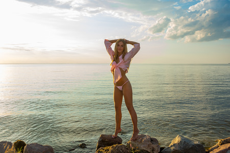 Beautiful happy young woman stands in a pink swimsuit and a shirt at the sea background at the sunset