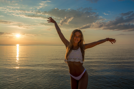 Beautiful happy young woman stands in a pink swimsuit and she rejoices with her hands up at the sea background at the sunset Stock Photo
