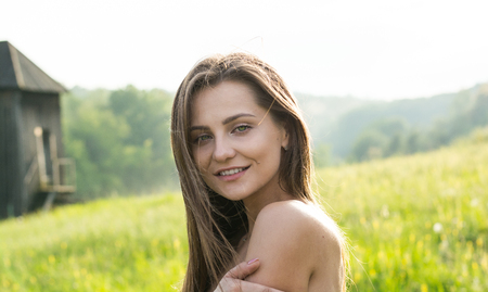 Portrait of a beautiful young woman with shoulders in the sunlight on a meadow with wildflowers at the rural background in summer.
