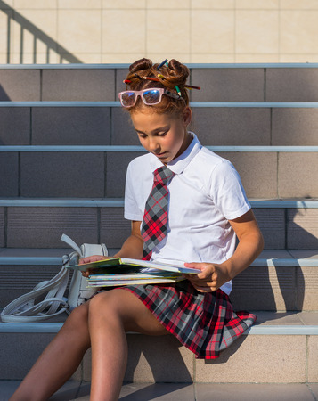 A girl in school uniform with a funny hairdo with colored pencils in her hair and with books sits on the steps in front of the school and reads the book, prepares for the lesson