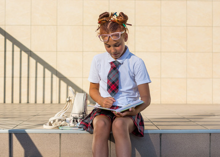 A girl in school uniform with a funny hairdo with colored pencils in her hair and with books sits on the steps in front of the school and reads the book, prepares for the lesson Banque d'images - 108202616