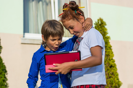 Children - a boy and a girl stand with tablet in the school yard and smile. The children look at something on the tablet. A boy and a girl are playing on tablets. Stock Photo