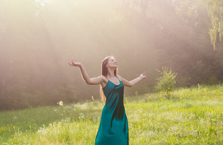 Young beautiful woman enjoys sunlight, raising her hands up on a flower meadow near the forest at sunset Stock fotó