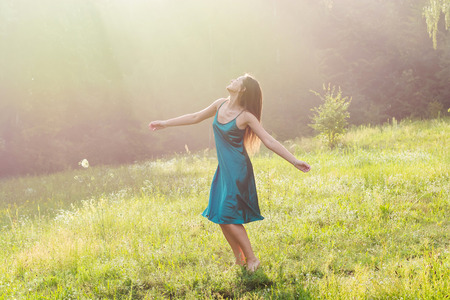 Beautiful smiling young woman is dancing and whirls barefoot on a flower meadow at sunset. Young beautiful woman enjoys sunlight, raising her hands up on a flower meadow near the forest at sunset Stock fotó