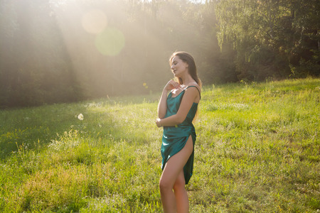 Young beautiful woman enjoys sunlight on a flower meadow near the forest at sunset