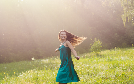 Beautiful smiling young woman is dancing and whirls on a flower meadow at sunset. Young beautiful woman enjoys sunlight, raising her hands up on a flower meadow near the forest at sunset Stock fotó