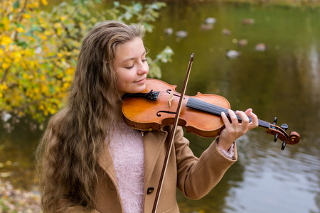 Girl playing the violin and smiling in the autumn park at a lake background. Young violinist playing in the park