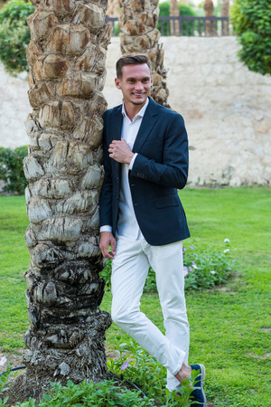 Young handsome laughing man in a white shirt, white trousers and suit stands near the palm tree. Fashion Model