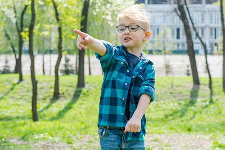Little surprised boy in glasses shows somewhere with a finger in spring park