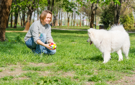 Young woman playing with a ball with a fluffy Samoyed dog and laughing in a park on the grass in spring