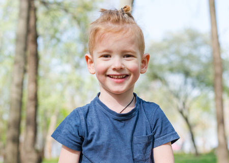 Portrait of a cute little boy who laughs in the park in spring