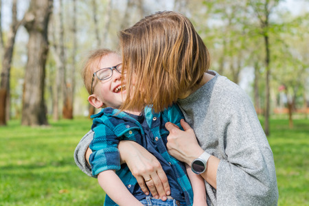 Mom kisses her little boy in the park on the grass in spring.