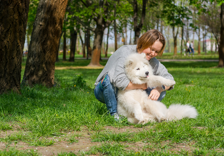 Young woman playing and hugging white fluffy samoyed dog and laughing in a park on the grass in spring