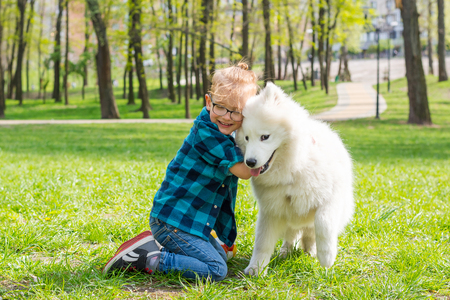 Little hipster boy in glasses hugging white fluffy samoyed dog and laughing in the park on the grass in spring