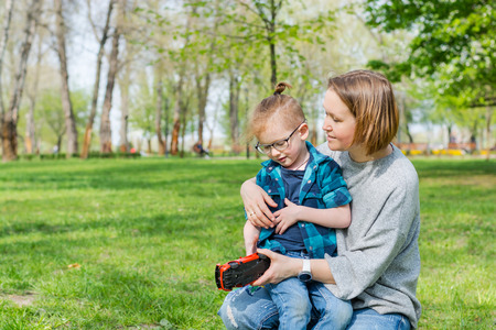 A little boy and his mom play with a toy car in the park on the grass in spring Imagens
