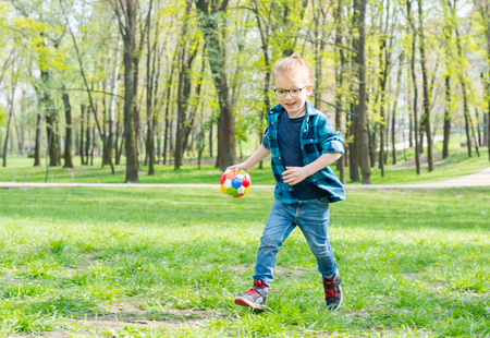 Little boy, hipster in a glasses with a ball run through the park on the grass in spring