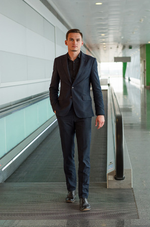A young handsome man in a suit got off the escalator in the airport. A young handsome man in a suit is walking along the airport corridor.