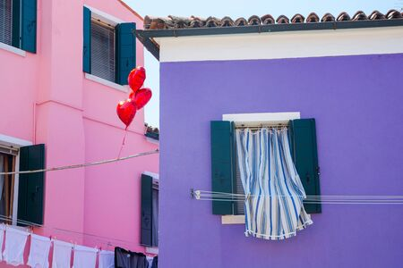 Window with curtains, heart-shaped balloons and colorful houses on the island of Burano, near Venice, Italy