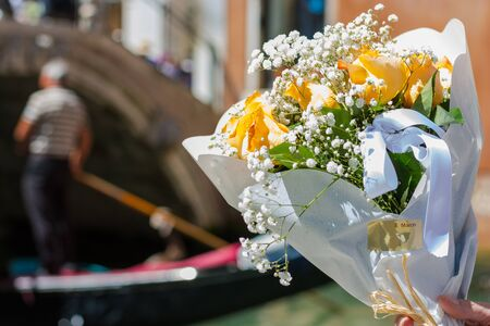 A bouquet of a orange roses at gondolier and Canal background in tne Venice, Italy