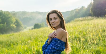 Beautiful young woman is laughing in the sunlight at the meadow with wildflowers background in summer.