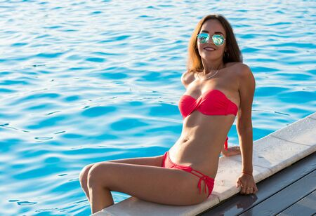 Beautiful young brunette woman with long wet hair in a sunglasses comes out of the pool