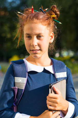 Girl stand with tablet near a school and reads. A girl in school uniform with a funny hairdo with colored pencils in her hair is stands near a school