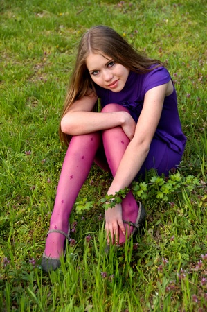 Beauty young girl is sitting on green grass