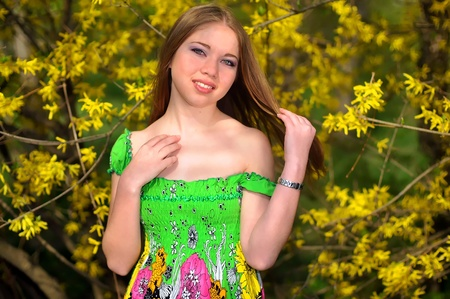 a portrait of a girl near blossoming yellow Forsythia bush Editorial
