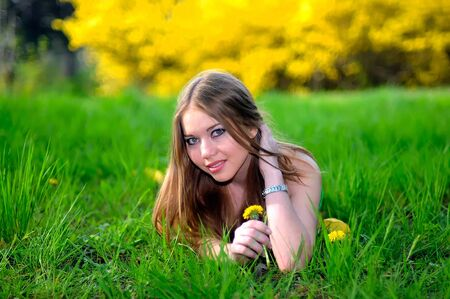 beauty young girl is laying on green grass