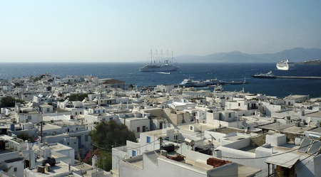 myconos: White houses descending to a bay from hills of Mykonos