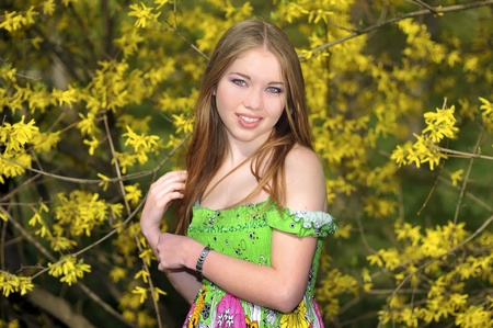 a portrait of a girl near blossoming yellow Forsythia bush Stock Photo