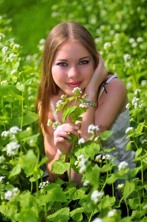 young girl is sitting on a green grass