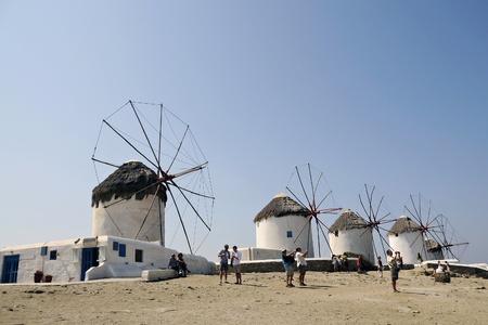Windmills on a green hillside near the sea. Mykonos. Greece