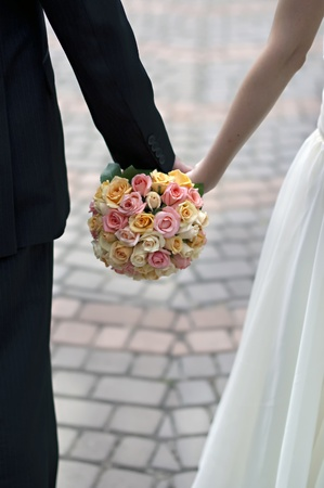 pink, orange and white wedding bouquet in the hands of the bride and groom