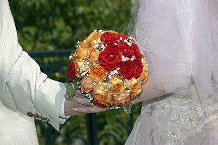 red, orange and white wedding bouquet in the hands of the bride and groom