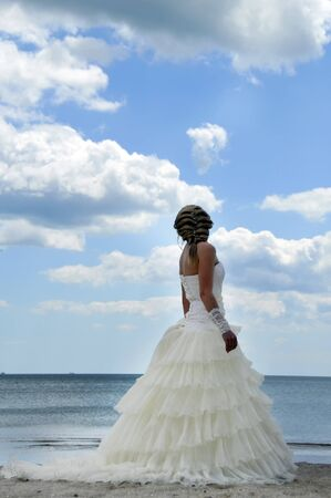 Beautiful young bride stands on the beach