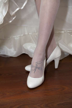 Abstract wedding composition - fiancee shows the dragon-fly tattoos and white shoes
