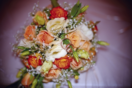 close-up of colorful wedding bouquet and two rings