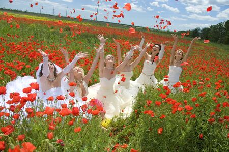 Annual event Bride Parade,  Happy excited participants in fiancees gowns take  blooming poppy field  Papaver Rhoeas  in celebration of marriage and romance Bride Parade on May 29, 2009 in Odessa,Ukraine
